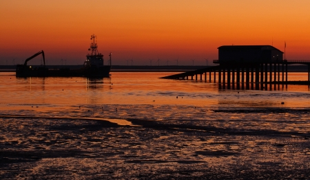 Boat returning to port at Barrow, passing the Roa Island RNLI jetty, with Walney Island in the Background 写真素材
