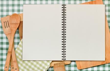 utensilios de cocina: Doble página de carpetas de anillas en blanco, con copia espacio gran telón de fondo las recetas en un guinga mesa verde con borde de equipo de cocina