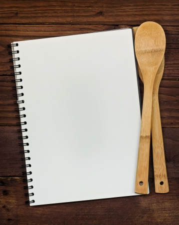 cooking ware: Empty ringbinder with copy space for menu or recipes, on a rustic wooden table top with kitchen utensils