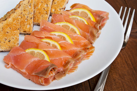 salmon ahumado: Salmón ahumado en lonchas con rodajas de limón intercalan y se sirve con pan tostado en un plato tradicional en un entorno de sobremesa restaurante rústico.