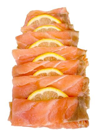 salmon ahumado: Salmón ahumado en lonchas y arreglado con rodajas de limón aisladas sobre un fondo blanco