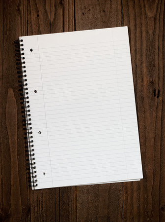 desk area: Empty lined ringbinder page with copy space for your message on a dark wooden desktop background