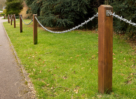 chain fence: Post and Chain fence down the side of a driveway a popular ornamental feature in gardens Stock Photo