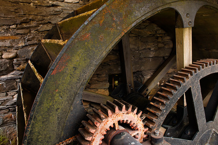 industrial heritage: Enclosed water mill wheel workings with ancient metal and wooden cog system part of industrial heritage. Stock Photo