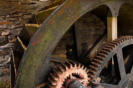 molino de agua: Funcionamiento de la rueda de molino de agua cerrado con antigua de metal y madera, parte del sistema de cremallera de patrimonio industrial.
