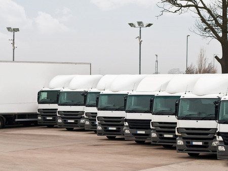 Company fleet of commercial lorries parked in a row ready for cargo distribution