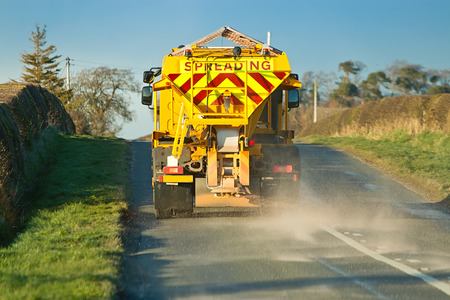 adverse: winter service vehicle or gritter spreading rock salt on the road surface to prevent icing in winter which causes accidents when vehicles slip on the highway. Stock Photo