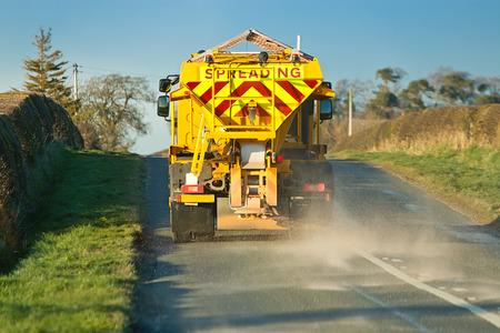 Winterdienstfahrzeug oder Streu Verbreitung Steinsalz auf der Fahrbahn, um das Vereisen im Winter, der Unfälle verursacht, wenn die Fahrzeuge rutschen auf der Autobahn zu verhindern. Standard-Bild - 27704924