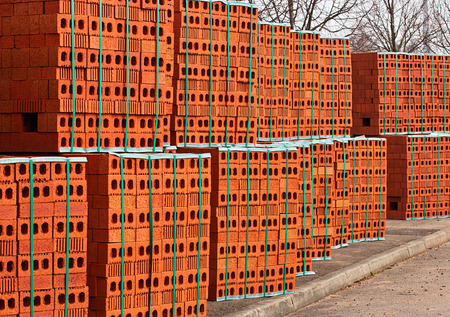 building material: Delivery of red bricks a popular building material ready for the construction of a new home by Builders