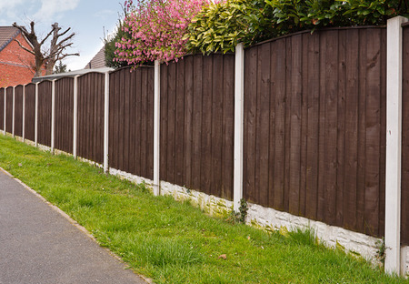 개인 정보 보호: 닫기 보드 울타리 나무 울타리 패널, 콘크리트 기둥 및 추가 내구성 킥보드와 개인 정보 보호를 위해 정원의 주위에 세워진.