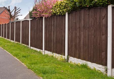 woonwijk: Sluiten schutting opgetrokken rond een tuin voor de privacy met houten hekwerk panelen, betonnen palen en kickboards voor extra duurzaamheid.