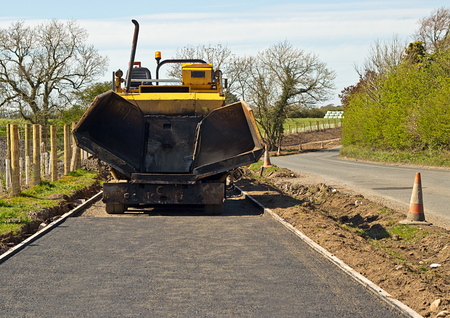 resurfacing: Small scale construction machinery laying a roadside footpath for greater pedestrian safety