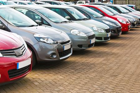Line-up van de verschillende soorten van gebruikte auto's te koop op een autohandelaren voorplein alle marques verwijderd