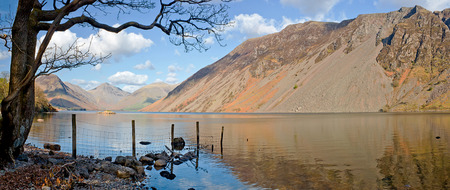 Wastwater, englands deepest lake located in the English Lake District, a scenic panoramic view showing the screes and view towards the foot of scafell pike englands highest mountain in the distance.