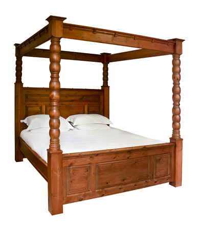 Traditional wooden Four Poster Bed isolated against a white background Standard-Bild