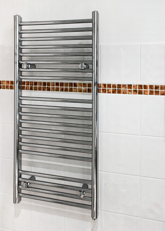 radiated: Chrome heated towel rail which serves a dual purpose as a radiator and towel dryer in modern bathrooms.