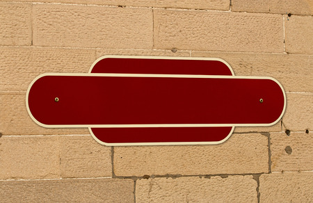 Traditional blank railway sign on the wall of a train station for insertion of your message or place name in middle. Standard-Bild