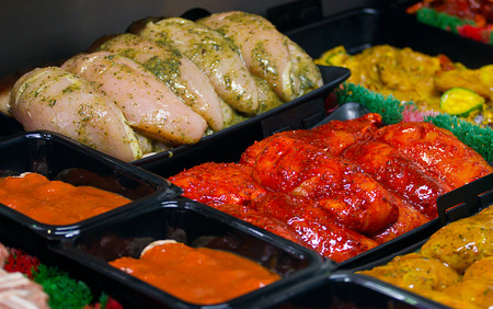 Fresh chicken fillets marinaded in chinese coatings on a Butchers display counter for making your own easy stir fries