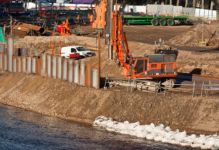 Industrial contractor completing public works and strengthening river bank flood defences with verticle steel piles