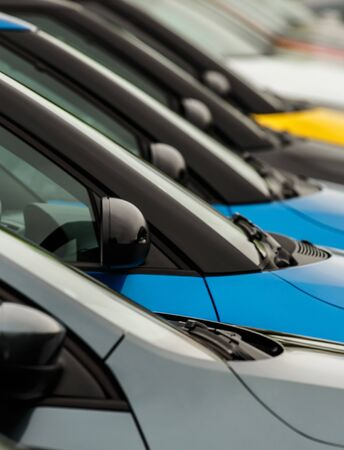 Vehicles for sale parked in a row with close up detail on the wing mirror without focus on any particular model making the cars generic and unidentifiable. A good concept for general car sales where a range of different manufacturers are on offer.