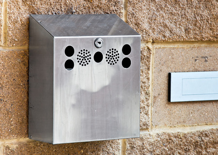 dispose: Wallmounted stainless steel cigarette bin on an exterior wall outside a place of work where smoking is banned inside. This enables smokers to extinguish and dispose of cigarettes in a tidy organised fashion.