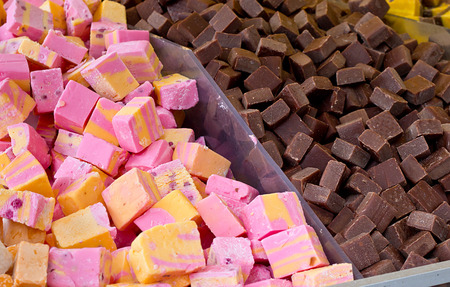 sweettooth: Selection of fudges for sale in a pick and mix counter where people select their own favourite penny mixtures from the wide range on display. Stock Photo
