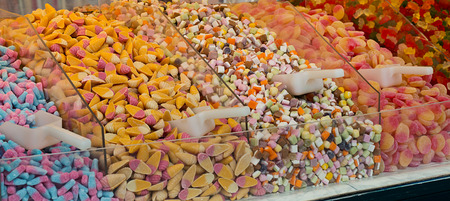 sweettooth: Selection of sweet candies for sale in a pick and mix counter at a sweetshop. A popular method of selling sweets where the customer can pick their own selection to match their sweet tooth. Stock Photo