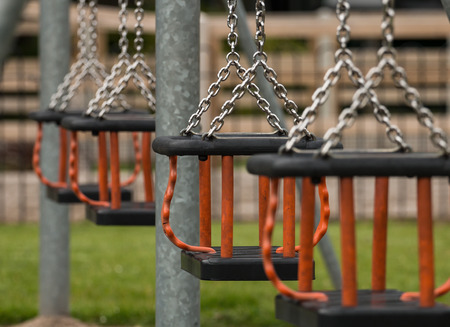 swing seat: Row of swing seats at a local play park or childrens playground provided by the local council for children to have fun in their community. Selective focus on a single Cradle seat.