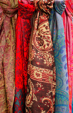 Celection of colorful head Scarves for sale on a rack at a market stall