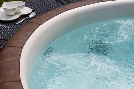Luxurious standalone hot tub or jacuzzi with hot bubbling water 写真素材