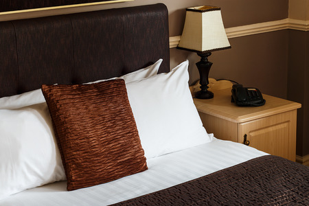 Generic hotel room example with freshly made bed, clean sheets and a plain neutral decor which can be found in any motel bedroom or bed and breakfast accommodation. Standard-Bild