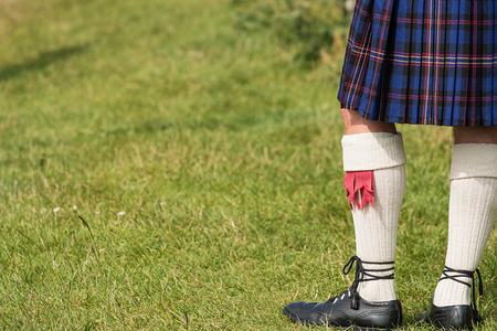 checkered skirt: Man dressed in traditional Tartan Kilt an example of Scotlands national costume