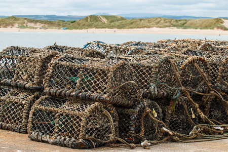 Lobster pots stacked in pile on a harbour with a sandy bay in the background Standard-Bild