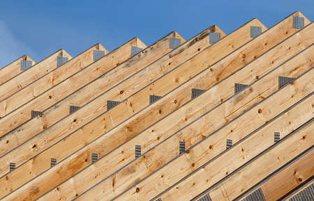 Row of Timber roof trusses in a line on a modern roof construction of a new build warehouse.
