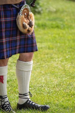 Bagpipe player dressed in Scottish National Dress including kilt and sporran with space for your text
