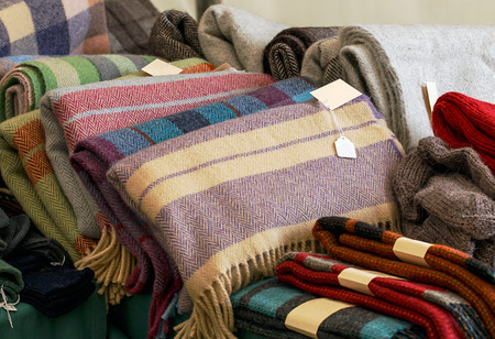 woven: Selection of throws traditionally made of wool in a pile for sale at market traders, great example of crafting industry.