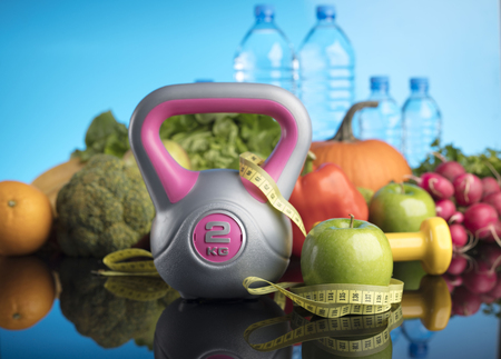 lowering: Diet and Fitness theme with healthy food. Beautiful reflections. Bright blue background. Lots of vegetables, fruits and fitness equipment. Healthy lifestyle concept.