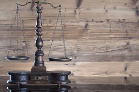 Law theme – scale of justice on wooden background
