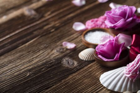 Roses and spa accessories on wooden table