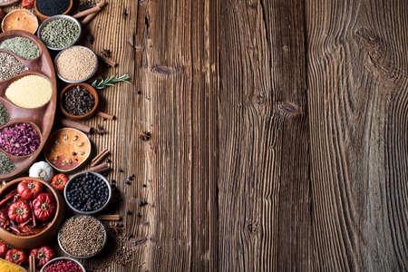 木製テーブルの上の鉢にカラフルなスパイスのセットです。
