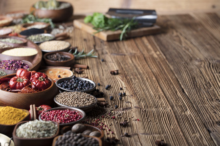 Set of colorful spices in bowls on wooden table. Stock Photo