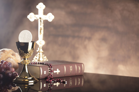 Catholic religion theme.  Holy Bible, the cross and gold chalice on stone table and stone background.