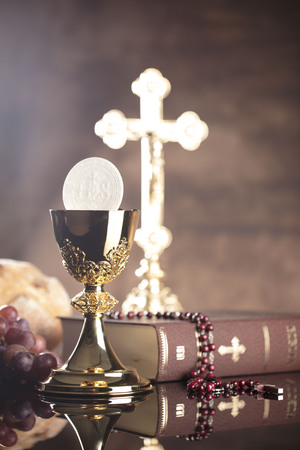 vestment: Catholic religion theme.  Holy Bible, the cross and gold chalice on stone table and stone background.