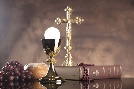 Catholic religion theme. Holy Bible, the cross and gold chalice on wooden table and stone background. Zdjęcie Seryjne