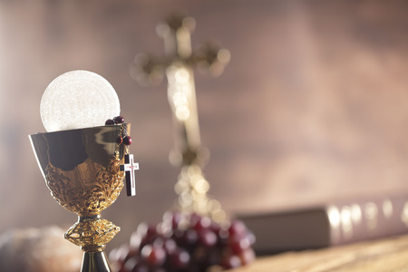 vestment: Catholic religion theme. Holy Bible, the cross and gold chalice on wooden table and stone background. Stock Photo