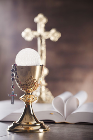 Holy Bible, the cross and gold chalice on stone table and stone background Stock Photo