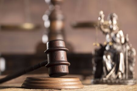 up code: Law and justice theme. Mallet of judge and scale of justice. Themis - statue of justice. Wooden table.