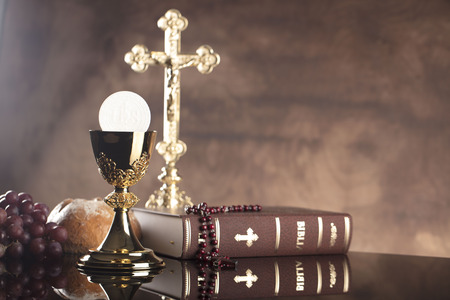 Holy Bible, the cross and gold chalice on stone table and background