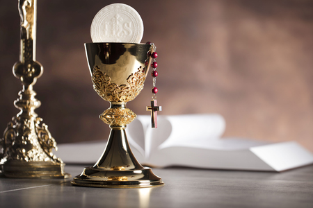 vestment: Holy Bible, the cross and gold chalice on stone table and background