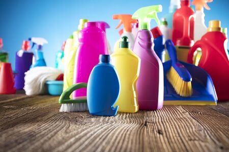 Spring cleanup theme. Variety of colorful house cleaning products on a rustic wooden table and blue background. Stock Photo